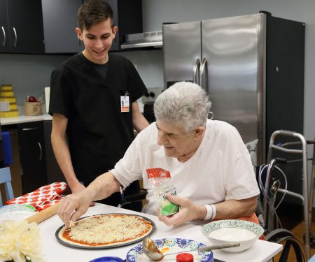 short-term care resident making pizza