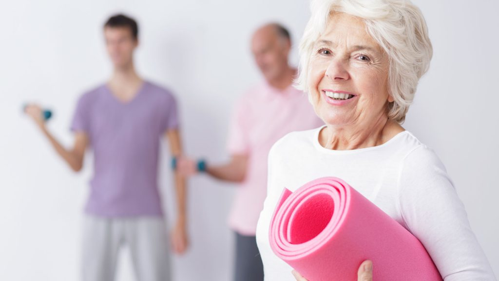 Older woman with yoga mat for American Heart Month