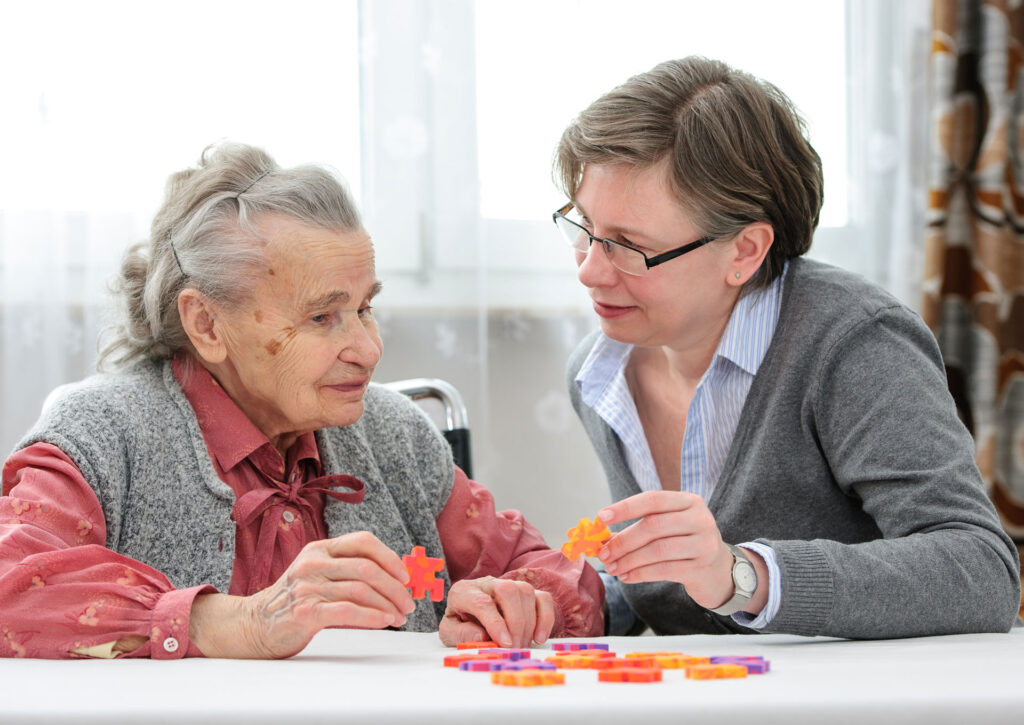 Nursing home resident solving a puzzle with a staff member