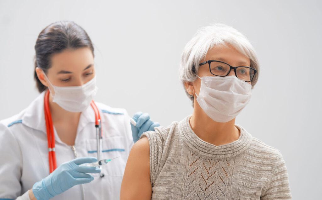 nurse administering COVID-19 vaccine to senior female