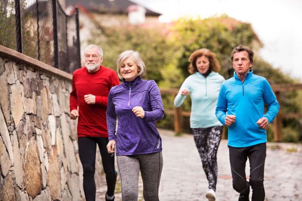 group of seniors jogging outside down a hill