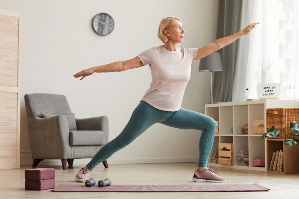 senior woman practicing a yoga stretch at home