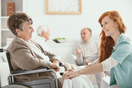 nurse helping senior woman in wheelchair inside a nursing home