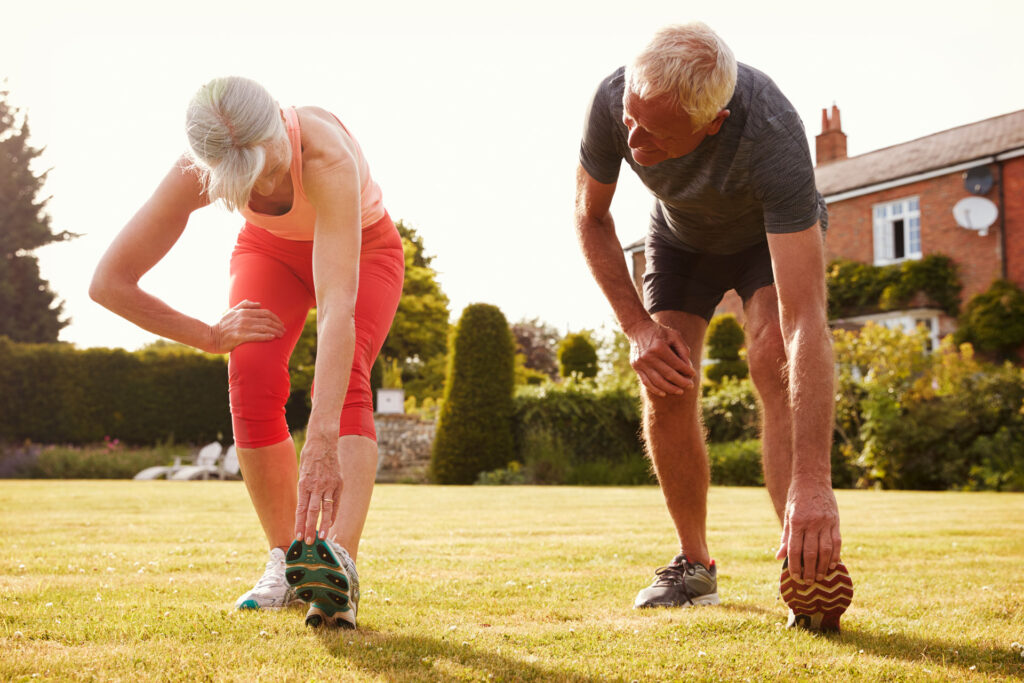 senior male and female stretching their legs on a lawn