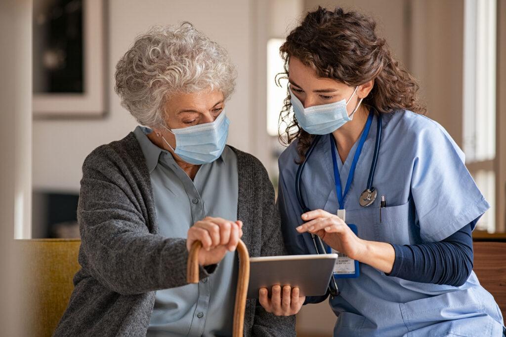 nurse meeting with nursing home resident wearing masks