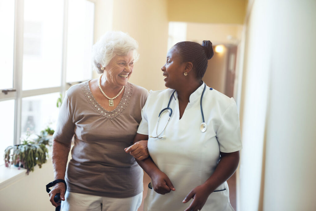 female nursing home resident walking with nurse