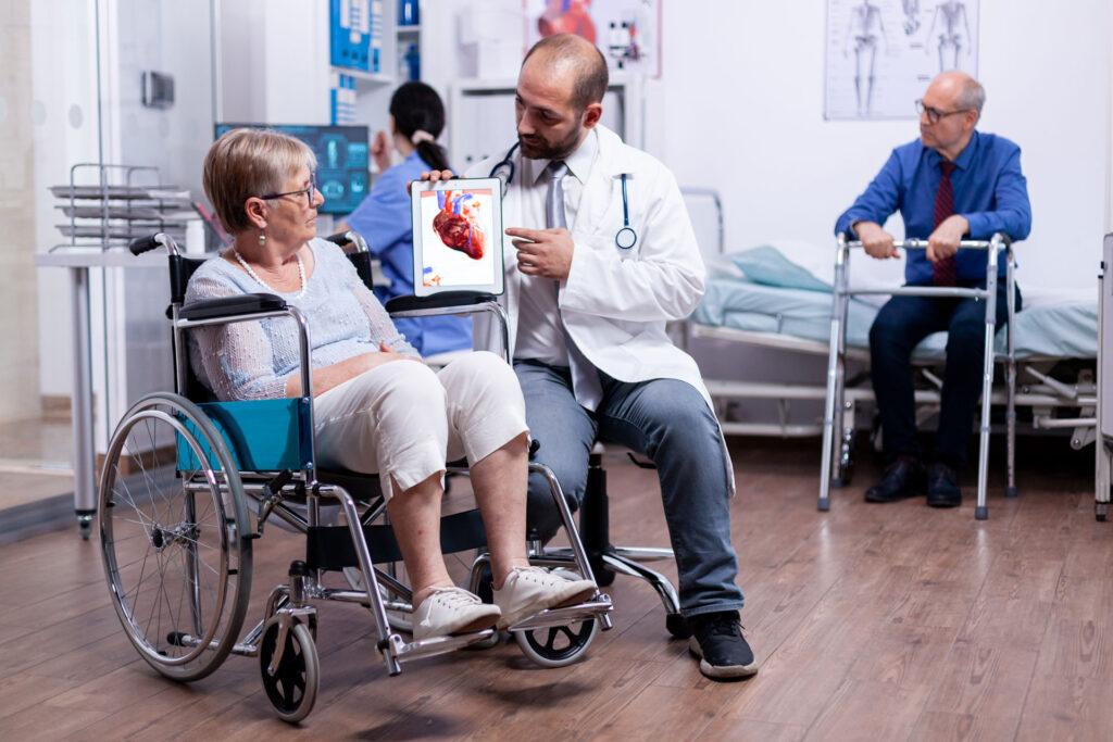 doctor explaining heart disease to female senior in wheelchair