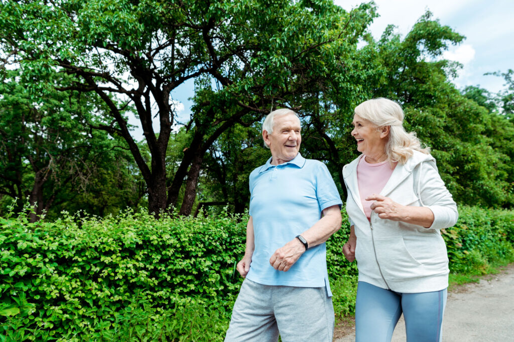male and female seniors briskly walking in a park