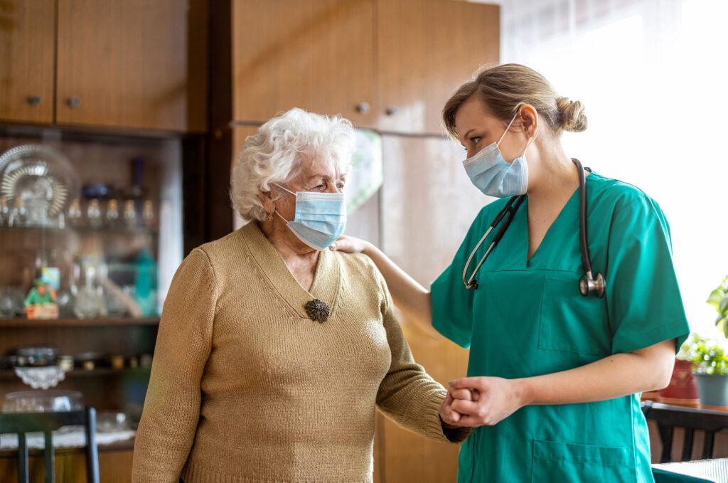 female nurse helping senior lady wearing face masks