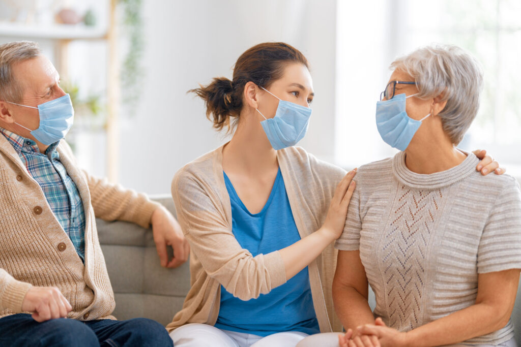 daughter with her parents wearing face masks sitting on a couch