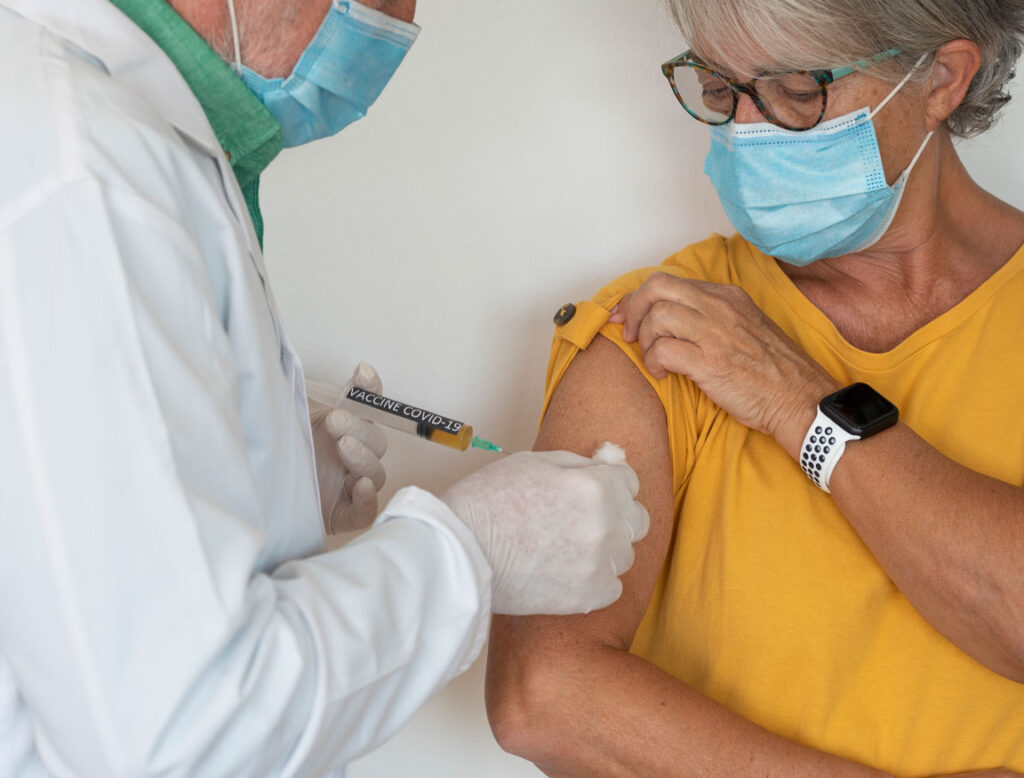 doctor injecting COVID-19 vaccine into senior female